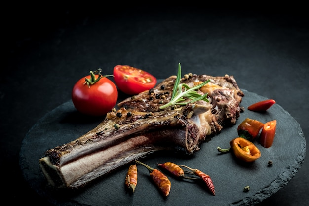Beef steak with rosemary, chili peeper and tomatoes on slate board
