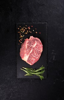 Beef steak with rosemary and pepper on a black table with copy space, vertical orientation