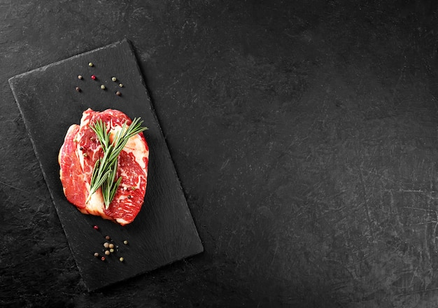 Beef steak with rosemary and pepper on a black table with copy space