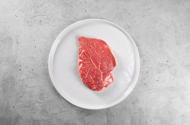 Beef steak with rosemary and pepper on a white plate with copy space
