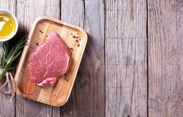 Beef steak with rosemary and pepper on on a wooden table, top view