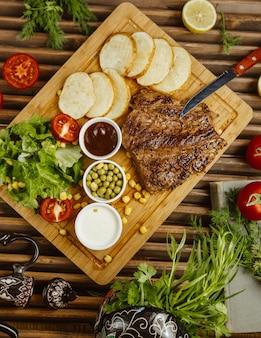 Beef steak with round roasted potatoes on a wooden table served with green salad, beans and mayonnaise