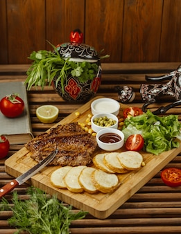 Beef steak with round roasted potatoes on a wooden table, side view,  with green salad, beans and mayonnaise