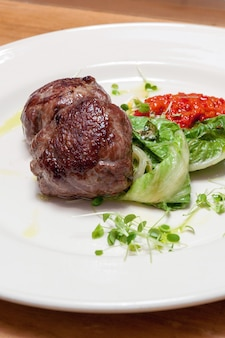 Beef steak with salad and vegetable sauce on a white plate
