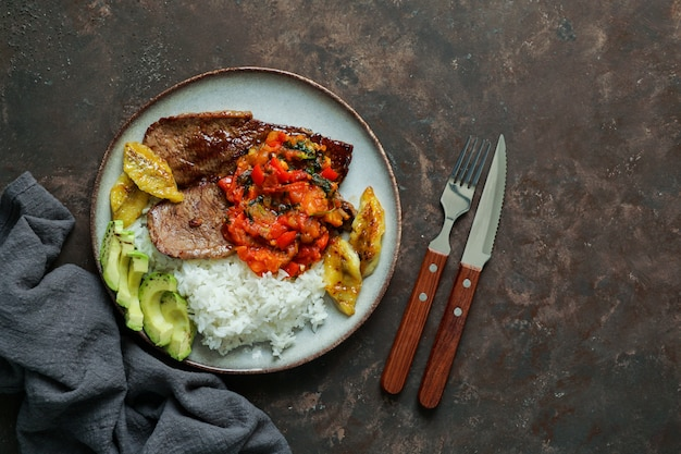 Beef steak with tomatoes sauce, rice, avocado, bananas fries