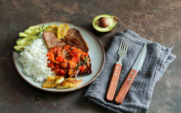 Beef steak with tomatoes sauce, rice, avocado and bananas fries