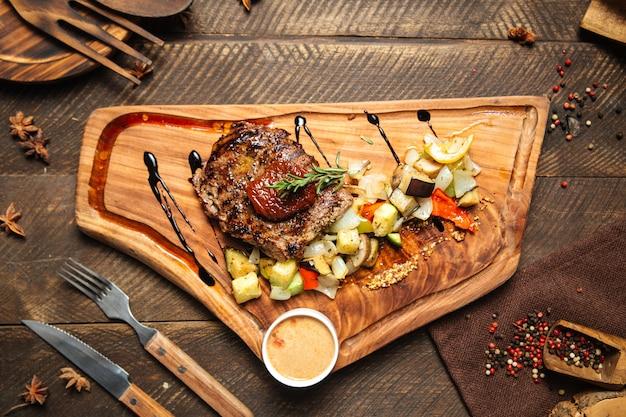 Стейк из говядины с овощами на деревянной доске