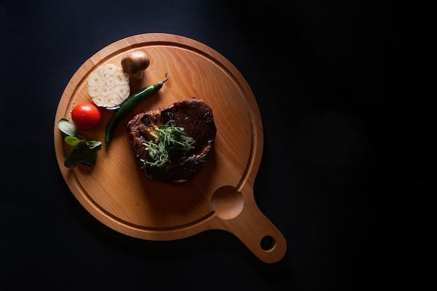 검은 표면에 고립 된 나무 보드에 야채와 쇠고기 스테이크