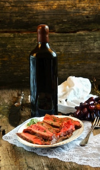 Beef steak on the wooden cutting board with grapes
