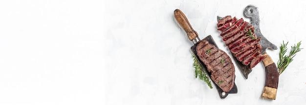 Стейки говядины на более мясном ноже мясника со специями светлом фоне. вид сверху. формат длинного баннера.