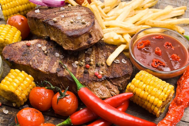 Стейки из говядины на деревянном столе