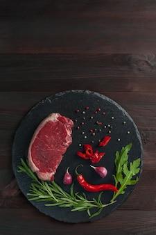 Стейки из говядины готовы к приготовлению, кулинарный фон. свежее сырое мясо на разделочной доске с розмарином, y