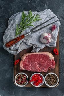Рибай стейки из говядины готовые к приготовлению, кулинарный фон. свежее сырое мясо на деревянной разделочной доске с розмарином, y