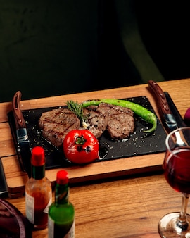 Beef steaks served with grilled tomato and pepper