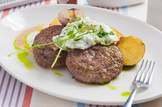 Стейки из говядины с картофелем и запеченным луком на белой тарелке