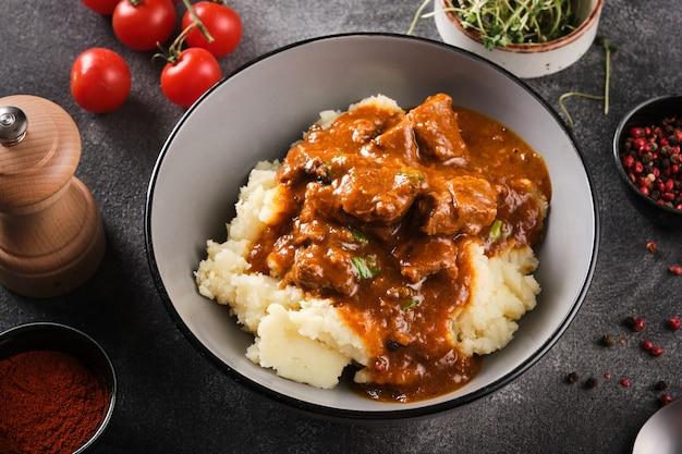 Тушеная говядина в томатном соусе с картофельным пюре. гуляш с соусом и картофелем.