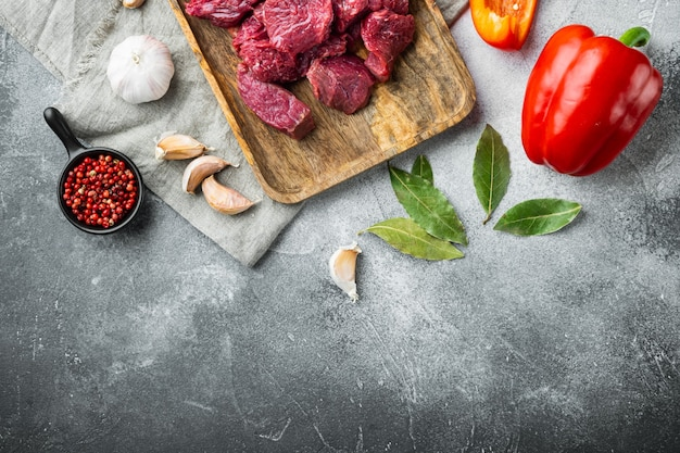 Beef stew raw ingredients set, on gray stone table, top view flat lay