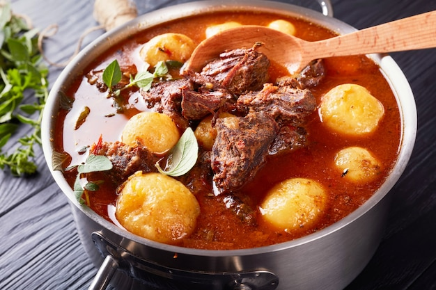 Beef stew with tender cubes of meat, whole new potatoes, carrots and herbs in a metal casserole on black wooden table with bouquet of aromatic herbs, view from above, close-up