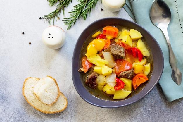 돌 그릇에 야채와 향신료와 쇠고기 스튜
