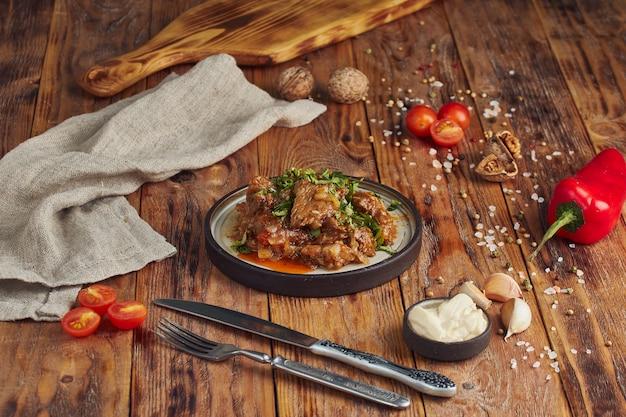 Тушеная говядина с овощами, грузинская кухня на деревянном столе