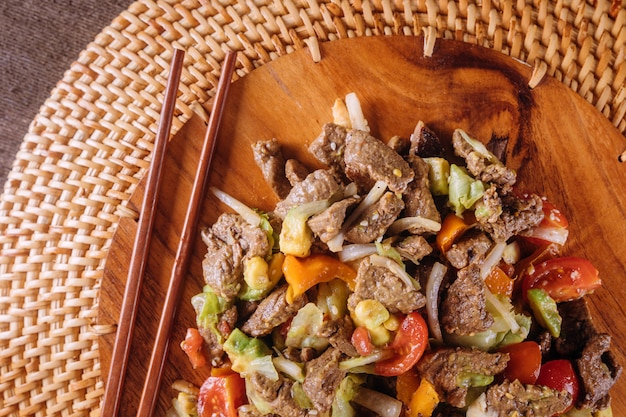 Beef stir-fry with bell peppers on wooden plate