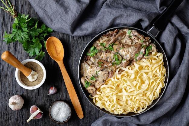 Бефстроганов, приготовленный со сметанным грибным соусом, подается с яичной лапшой на сковороде на темном деревянном столе, плоская, горизонтальный вид сверху