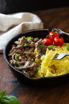 Beef stroganoff in a frying pan on dark rustic wooden.