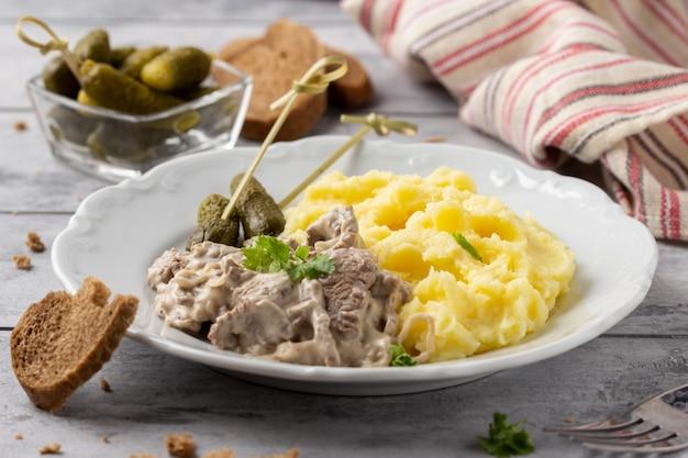 Бефстроганов с говядиной в сливочном соусе, картофельным пюре и солеными огурцами