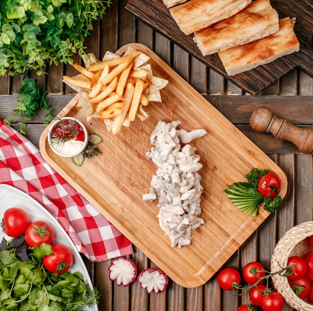 Бефстроганов с картофелем фри на деревянной доске