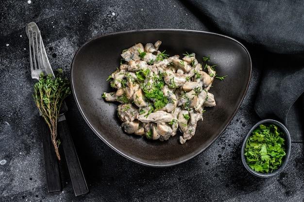 크레 미니와 샴 피뇽을 곁들인 접시에 버섯을 넣은 쇠고기 스트로가 노프. 검정색 배경. 평면도.