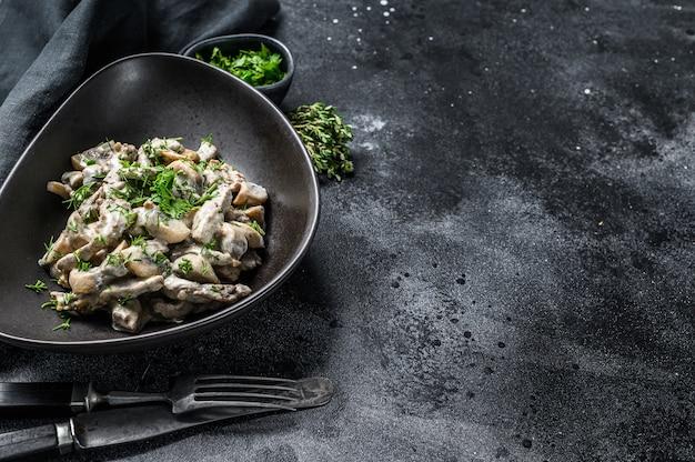 Бефстроганов с грибами в тарелке с кремини и шампиньонами
