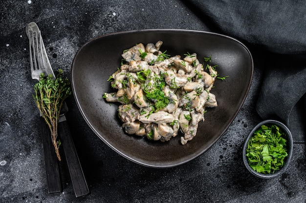 Beef stroganoff with mushrooms in a plate with cremini and champignons. black background. top view.
