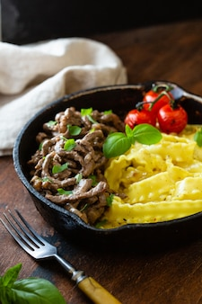 Beef stroganoff with tomato, basil and pasta.