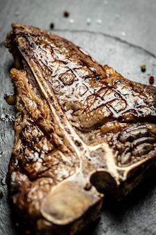 Beef t-bone сочный стейк из редкой говядины со специями. американская кухня. концепция приготовления мяса. средне-редкий стейк на гриле с ти-боун, портерхаус вагю, выдержанный на гриле.