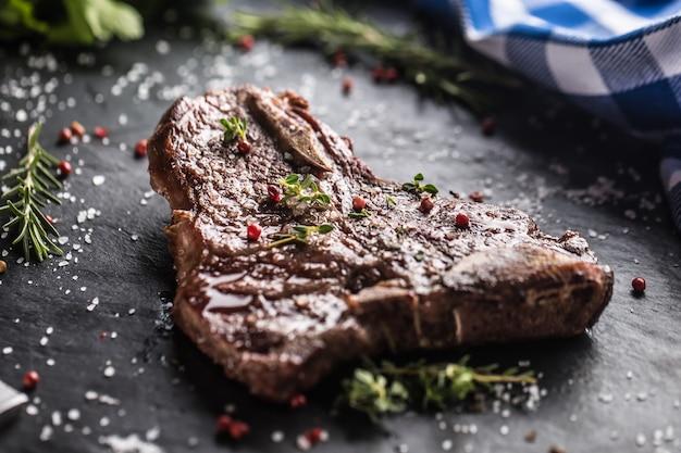 Стейк t-bone из говядины с соленым перцем и розмарином на грифельной тарелке.
