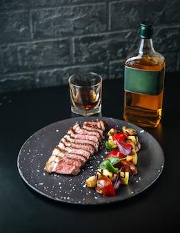 Тальята из говядины с картофелем и помидорами и зеленью на черной тарелке с виски