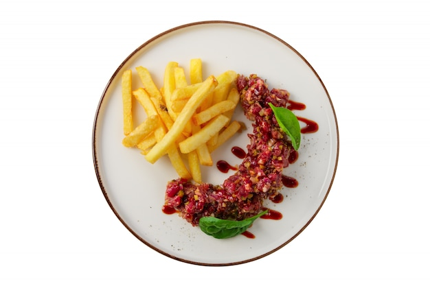 Beef tar tar  with balsamic sauce, basil and french fries isolated on white