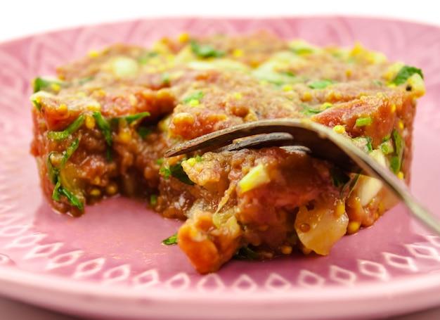 ピンクのプレートに牛肉のタルタルステーキをクローズアップ。セレクティブフォーカス。スペースをコピーします。レストランメニューのコンセプト