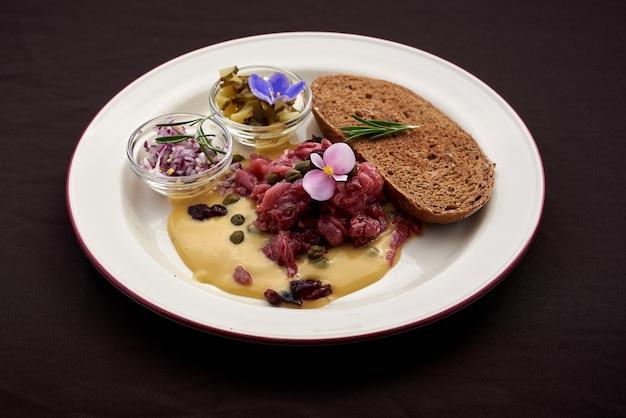 Тартар из говядины с яичным желтком, каперсами, солеными огурцами и луком Premium Фотографии
