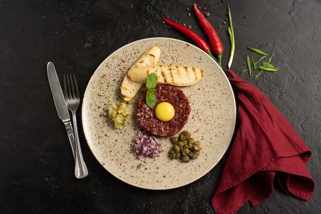 Тартар из говядины с луком, яйцом и белым хлебом. холодное блюдо из сырой говядины с яйцом и луком на черном столе. вид сверху.