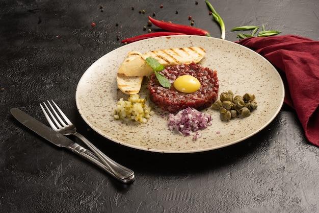 Тартар из говядины с луком, яйцом и белым хлебом. холодное блюдо из сырой говядины с яйцом и луком на черном столе.