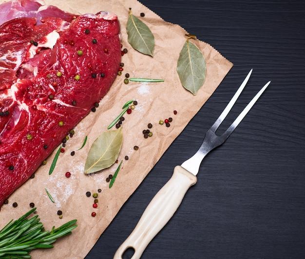 Beef tenderloin on brown kraft paper and a kitchen fork