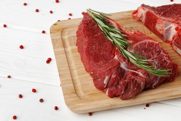 Вырезка говядины на деревянной доске на деревянном столе