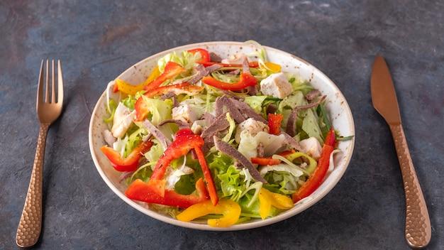 Говяжий язык, куриное филе и свежие овощи на тарелке