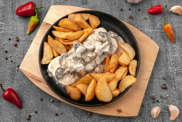 Beef tongue in creamy mushroom sauce with baked potatoes in a rustic way in a castiron pan