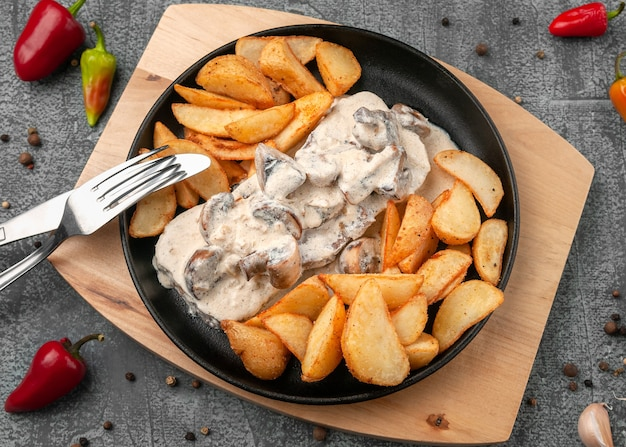 Beef tongue in creamy mushroom sauce with baked potatoes in a rustic way