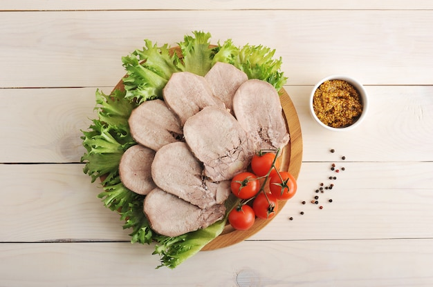 Beef tongue on a platter with lettuce leaves, cherry tomatoes and dijon mustard