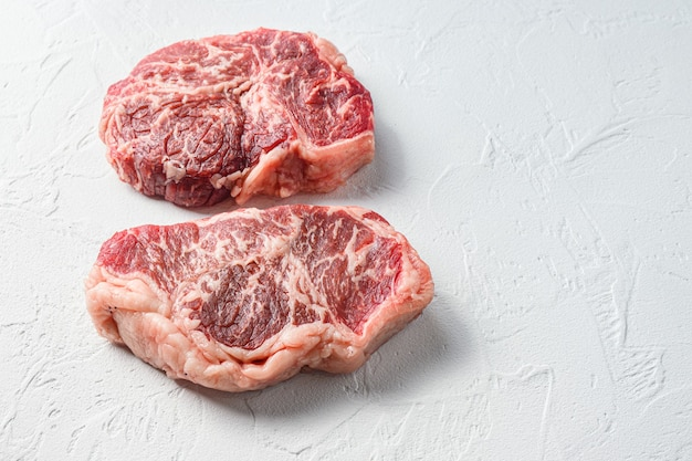 Beef  top blade steak, organic meat. white textured background. side view with space for text.