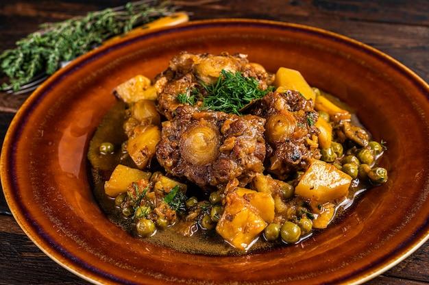 Тушеное мясо из говяжьих хвостов с овощами в деревенской тарелке