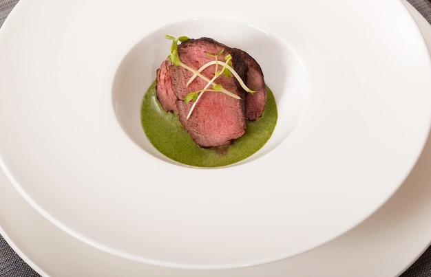 Говядина с зеленым соусом на белом блюде